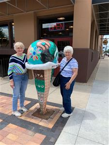 Two Heritage Club members pose in front of an ice cream statue.